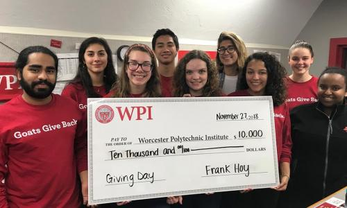 Members of the WPI community hold up an oversized check for $10,000 made out to WPI from Foisie Business School professor Frank Hoy. alt