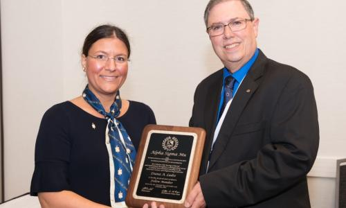 Diana Lados accepts a plaque noting her election as a fellow of Alpha Sigma Mu, the international professional honor society for materials science and engineering, from ASMu president Joe Newkirk at Materials Science & Technology 2018. alt