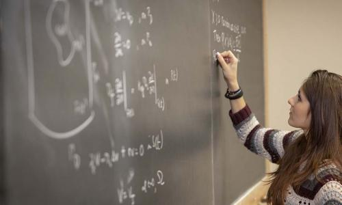 A woman writes a math equation on a chalkboard that already features many different equations and formulas.