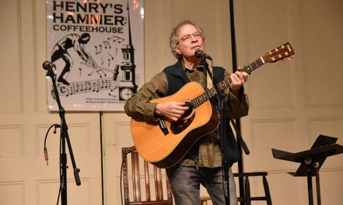Rick Quimby performing at an open mic with his guitar.