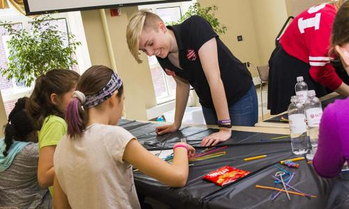 Kate Schweikert smiles as she helps two young girls with a project during a hands-on activity.