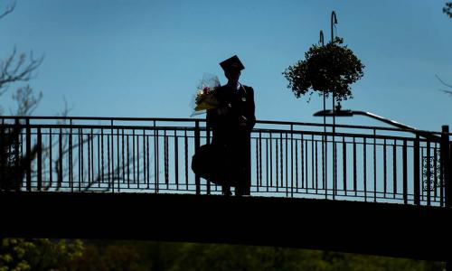 A silhouette of a graduate standing on top of Earle Bridge.