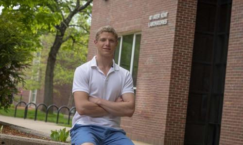 Matthew Adiletta sitting outside on a railing