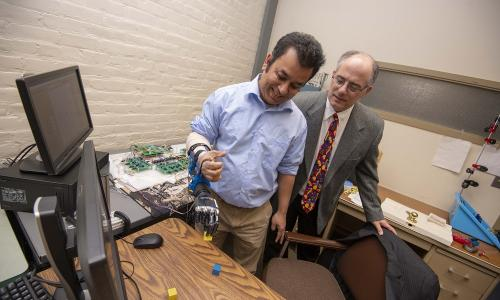Ted Clancy (right), professor of electrical and computer engineering at WPI, is developing wireless sensors to communicate with a prosthesis. alt