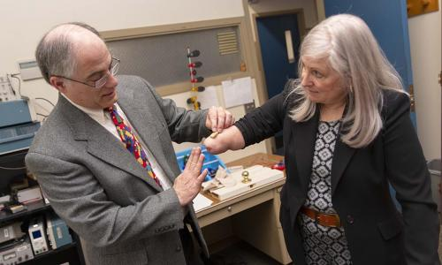 WPI professor Ted Clancy and consultant Debi Latour have had a longstanding partnership on prosthetics research. In this scene, Clancy places a wireless sensor on Latour's arm. alt