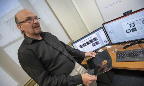 Randy Paffenroth, associate professor of mathematical sciences at WPI, holds a carbon-based sheet known as Miralon®, which is used in a variety of spacecraft applications. alt