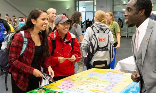 Students laugh together while learning about a project center at last year's Global Fair.