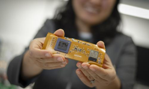 Professor Ulkuhan Guler shows off an early prototype of the miniaturized, wearable device that will one day monitor infants' blood oxygen levels. alt