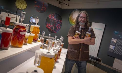 Professor Joshua Rosenstock, standing in his Fermentophone exhibit at the Harvard Museum of Natural History.  alt