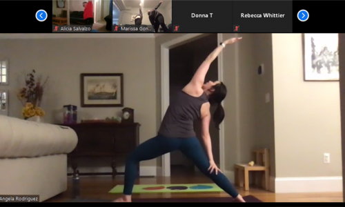 Angela Rodriguez, assistant professor of psychology, guides her yoga class into a Reverse Warrior pose.  alt