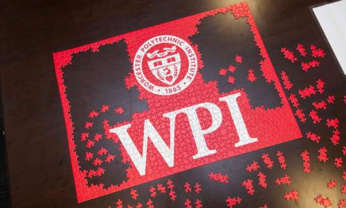 An aerial photo of a red WPI puzzle in the process of being completed.