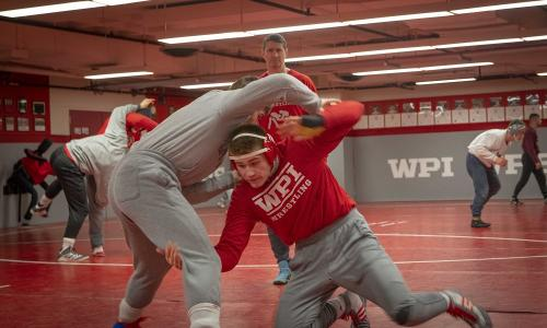 WPI wrestler Tyler Marsh practices a move under the watchful eye of Coach Matt Oney. alt
