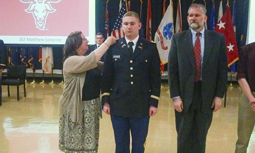 Army 2nd Lt. Matthew Sherrer of Wellesley has his gold bars pinned on by his parents, Janet and Stephen Sherrer. alt