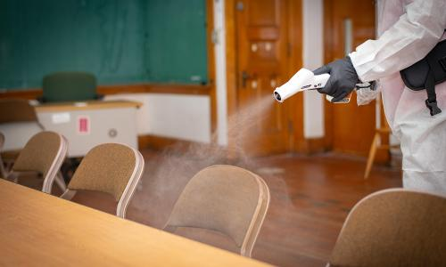 Worker sprays sanitizing mist onto table alt