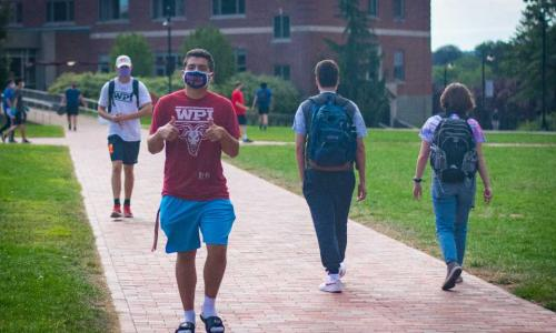Students walk through the Quad wearing face coverings and maintaining social distance. One flashes two thumbs up at the camera.