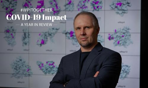 WPI researcher Dmitry Korkin stands in front of image of coronavirus alt