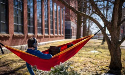 A student lounges in a hammock while working on a laptop.
