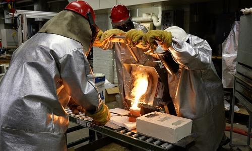 WPI researchers pour molten metal into a preheated investment casting mold. alt