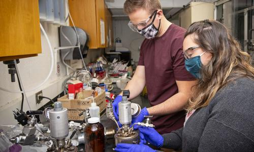 WPI PhD candidate Heather LeClerc (foreground) and WPI PhD student David Kenney work together to seal and prepare the reactor used to produce bio-oil from toxic sludge. alt