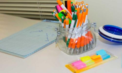 A photo of several pens in a cup on a table with sticky notes next to it.