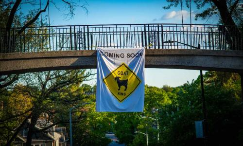 "A photo of a banner hanging on Earle Bridge that reads ""Coming Soon: Goat X-ing"""