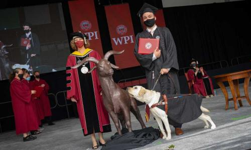A student and their service dog stand next to President Leshin to accept their diploma.